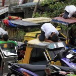 Muslim youths pray atop motorcycle taxis during the fasting month of Ramadan in front of Al-Satie Mosque in Baseco, Tondo city, metro Manila,