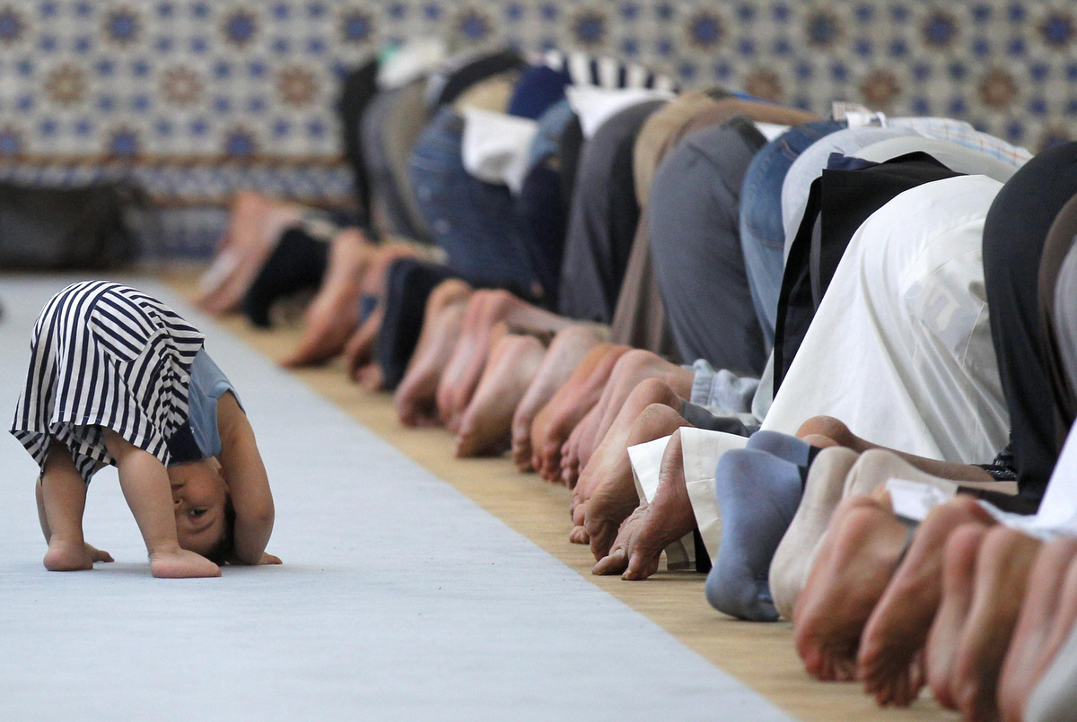 A child is seen near members of the Muslim community attending midday prayers at Strasbourg Grand Mosque in Strasbourg on the first day of Ramadan July 9, 2013. The Grand Mosque of Paris has fixed the first day of Ramadan as Wednesday, splitting with the French Council of Muslim Religion (Conseil Francais du Culte Musulman or CFCM), which determined it would begin on Tuesday.  (Vincent Kessler/Reuters)