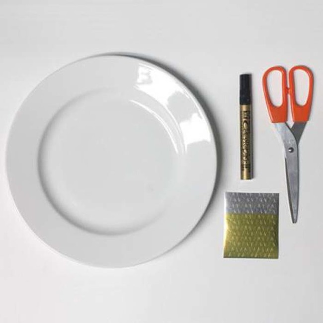 Start with a plate, a gold paint pen, a pair of scissors, and a sheet of star stickers.