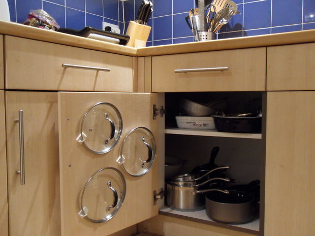 Keep pot lids orderly by mounting them via hooks on your cupboard doors.