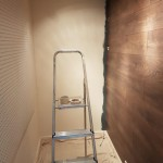 He began painting the adjacent wall before finishing the laminate to make the paint process easier later on.