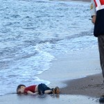 A Turkish police officer stands next to a migrant child's dead body (Aylan Shenu) papersnack.com