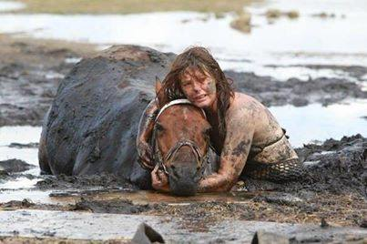A woman helping a horse who got stuck in mud.